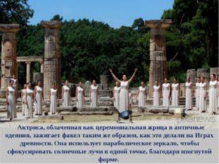 Актриса, облаченная как церемониальная жрица в античные одеяния, зажигает ф