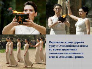 Верховная жрица держит урну с Олимпийским огнем во время церемонии зажжения о