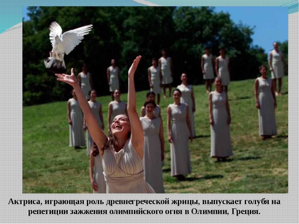 Актриса, играющая роль древнегреческой жрицы, выпускает голубя на репетиции з...
