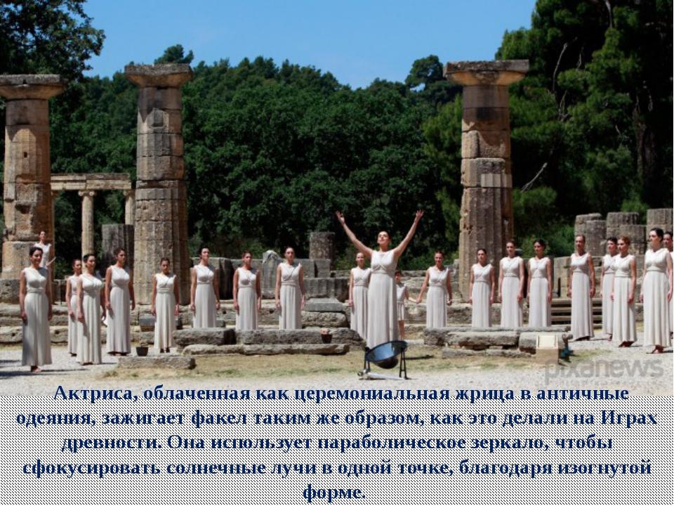 Актриса, облаченная как церемониальная жрица в античные одеяния, зажигает ф...