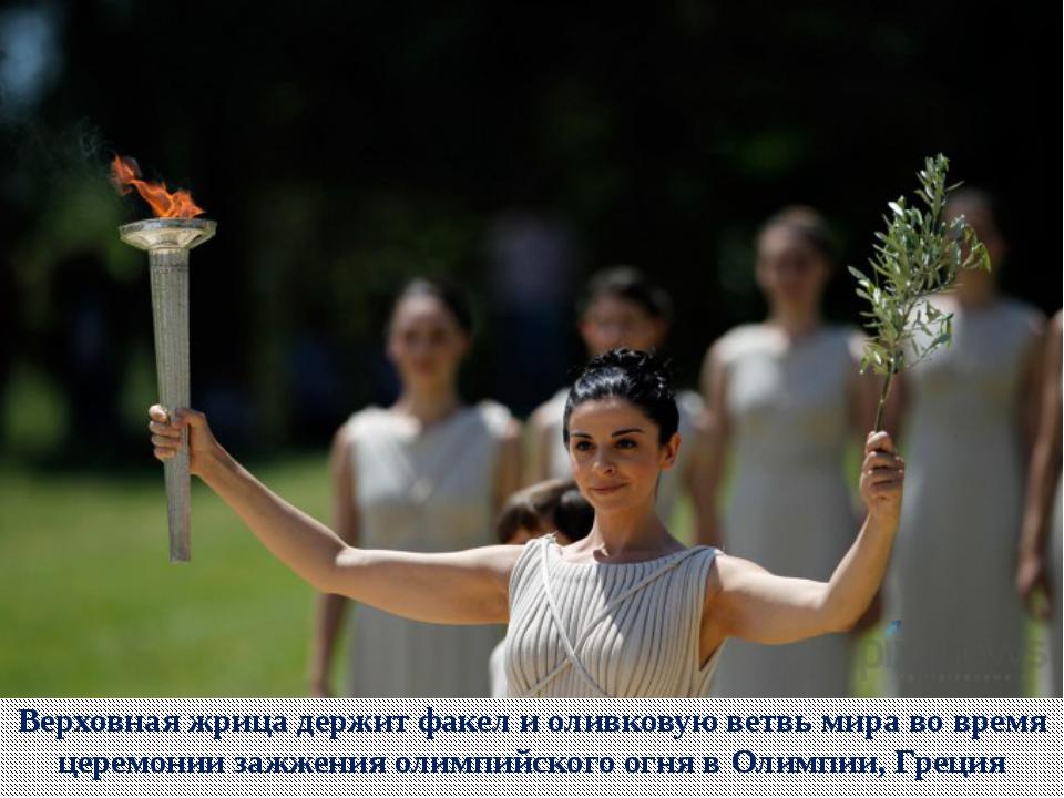 Верховная жрица держит факел и оливковую ветвь мира во время церемонии зажжен...