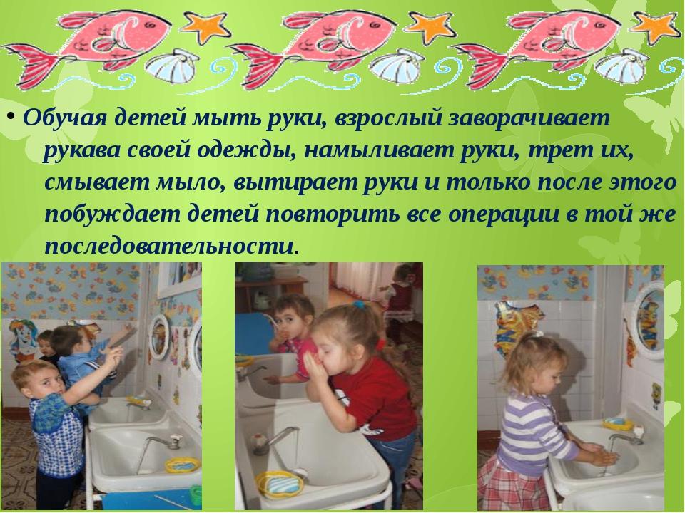 Обучая детей мыть руки, взрослый заворачивает рукава своей одежды, намыливае...
