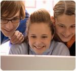 Трое детей смотрят на монитор компьютера