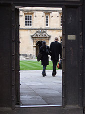 The tranquillity of an Oxbridge college glimpsed through an open wicket gate in the outside oak door. Paving stones lead to a grass quadrangle in front of an old two-storey building in yellow-pink stone, with sash windows on the upper floor above a passage entrance decorated with rococo carving and painted crest, leading to another grassed quadrangle. A male and female student, similarly dressed in short black coats, are walking in step away from the gate and into the depths of the college carrying their bags and holding hands.