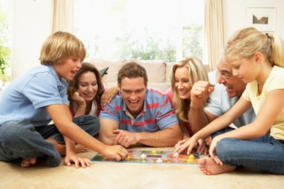 Family Playing Board Game At Home With Grandparents Watching…