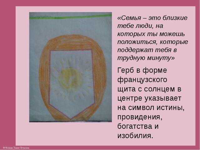 Герб в форме французского щита с солнцем в центре указывает на символ истины,...
