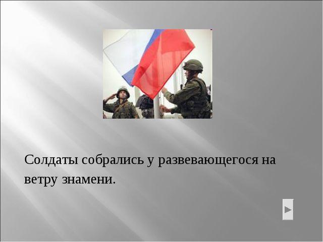 Солдаты собрались у развевающегося на ветру знамени.