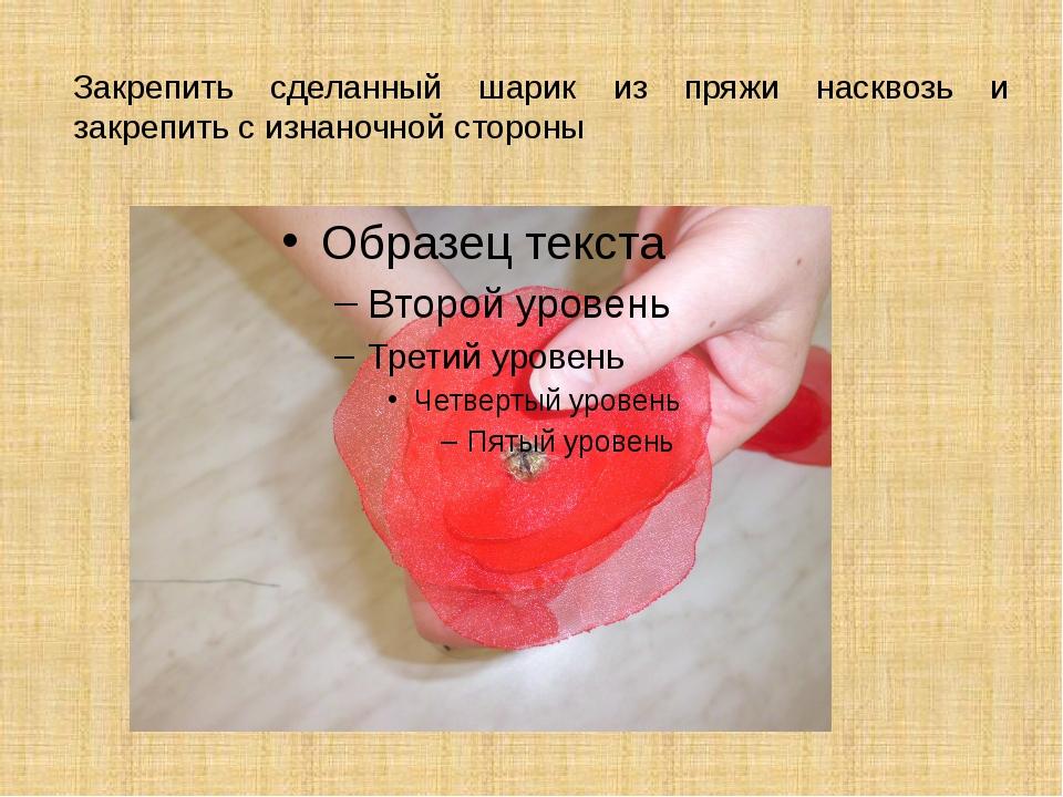 Закрепить сделанный шарик из пряжи насквозь и закрепить с изнаночной стороны
