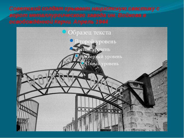 Советский солдат срывает нацистскую свастику с ворот металлургического завода...