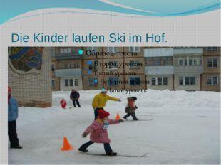Die Kinder laufen Ski im Hof.
