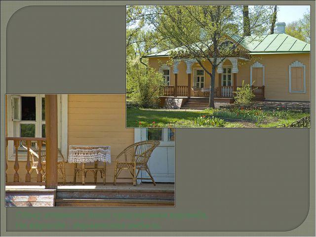 Сбоку главного дома пристроена веранда. На веранде - деревянная мебель.