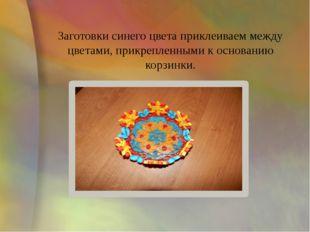 Заготовки синего цвета приклеиваем между цветами, прикрепленными к основанию