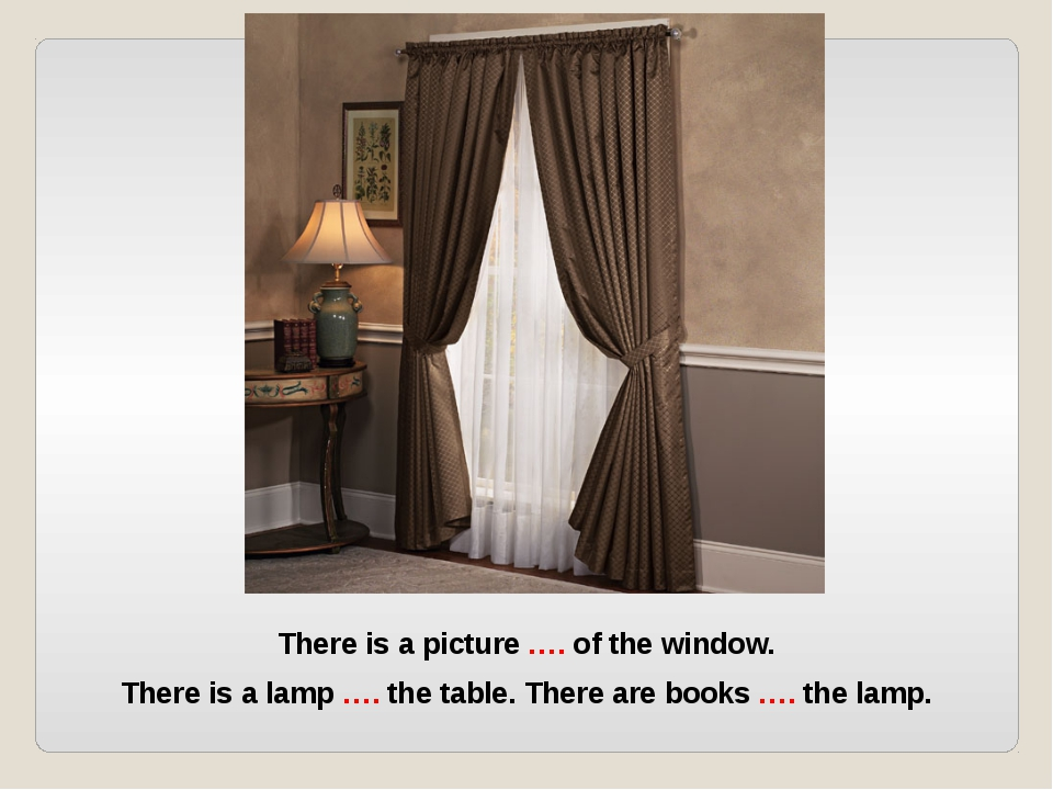 There is a picture …. of the window. There is a lamp …. the table. There are...