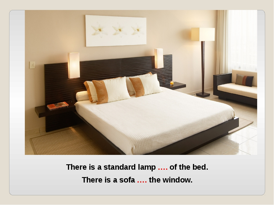 There is a standard lamp …. of the bed. There is a sofa …. the window.
