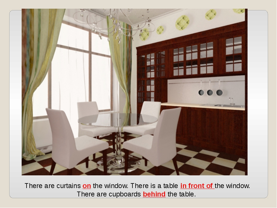 There are curtains on the window. There is a table in front of the window. Th...