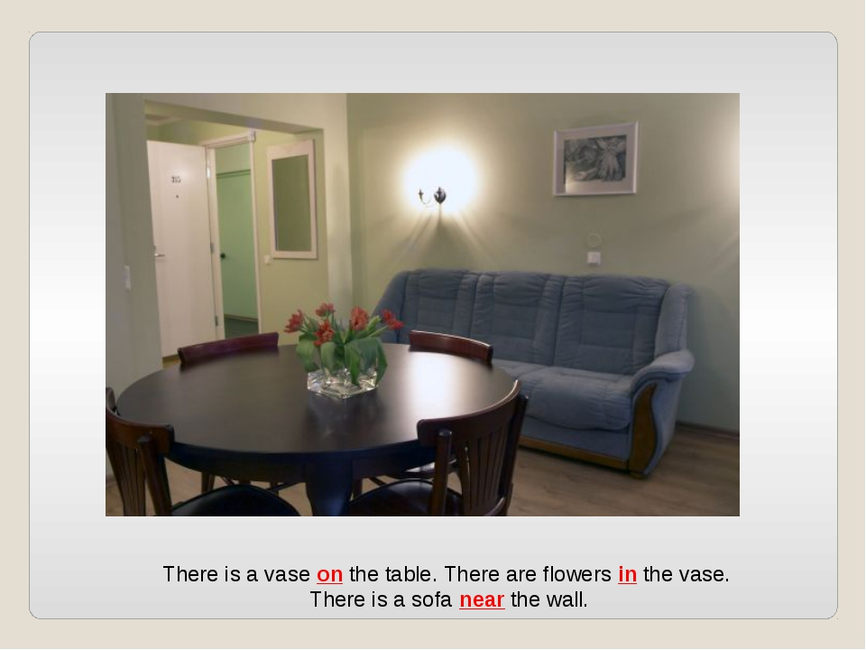 There is a vase on the table. There are flowers in the vase. There is a sofa...