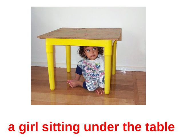 a girl sitting under the table