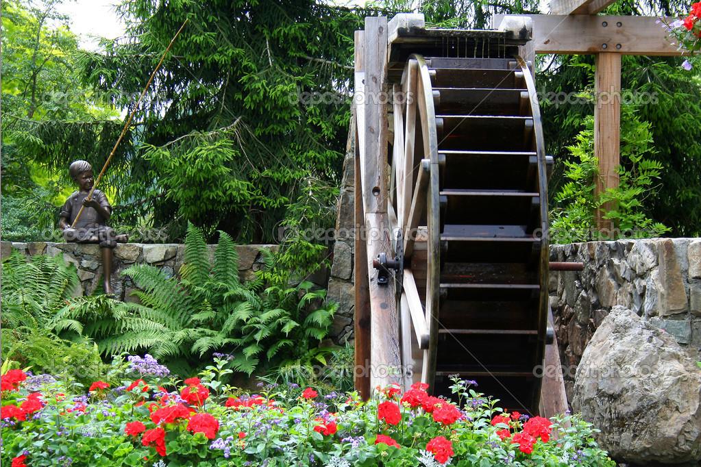 Водяное колесо в цветочном саду - Стоковое изображение: 5445420
