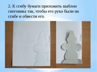 2. К сгибу бумаги приложить шаблон снеговика так, чтобы его рука были на сгиб