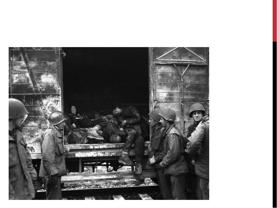 Американские солдаты молча осматривают железнодорожные вагоны с мертвыми тела...