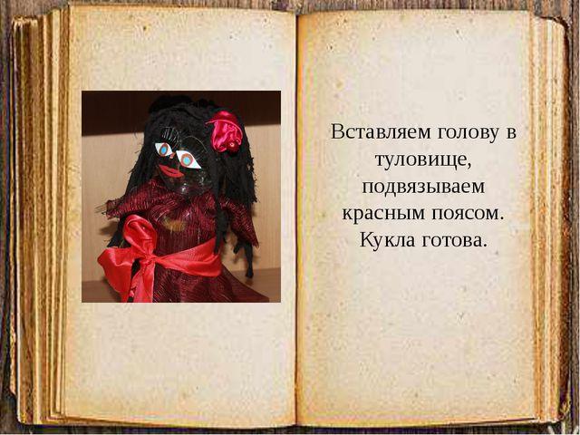 Вставляем голову в туловище, подвязываем красным поясом. Кукла готова.